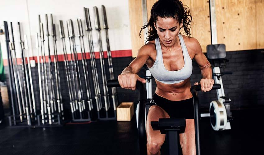 fit-young-female-working-out-on-gym-bike-PUTXKTG