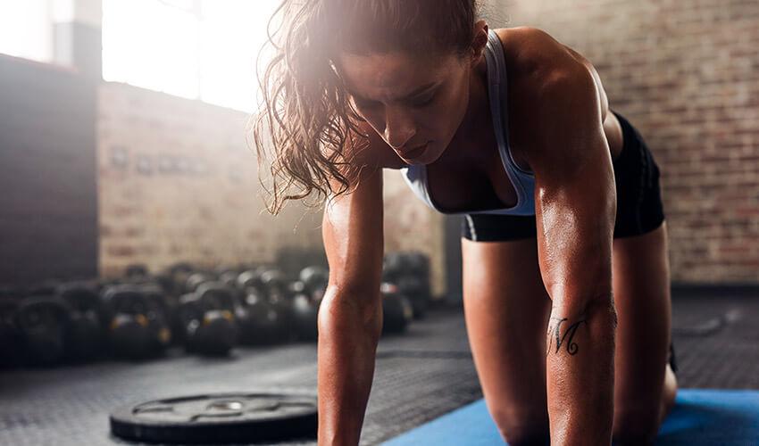muscular-woman-exercising-at-fitness-club-PL2ATRD