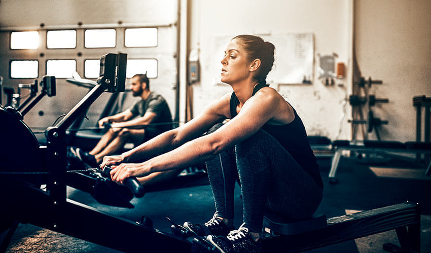 two-fit-people-exercising-on-rowing-machines-at-t